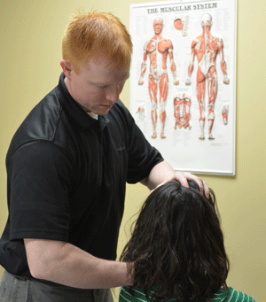 Shane Jackson, DPT, teaches a patient the correct posture to relieve her migraines.