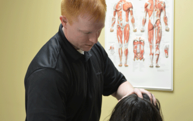 Shane Jackson, DPT, works with a patient on posture.
